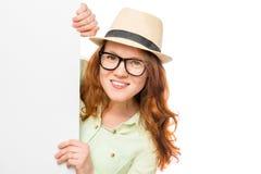 Het modieuze meisje kijkt uit van achter affiche Royalty-vrije Stock Foto's