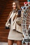 Het modieuze meisje kleedde zich in beige gebreide kleding, korte schapehuidlaag en handschoenengangen in het park op de zonnige  royalty-vrije stock fotografie