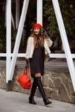 Het modieuze meisje kleedde zich in modieuze grijze kleding, korte schapehuidlaag, handschoenen en rode baret binnen houdend een  royalty-vrije stock afbeelding