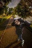 Het modieuze meisje rollerskating in het park Royalty-vrije Stock Afbeeldingen