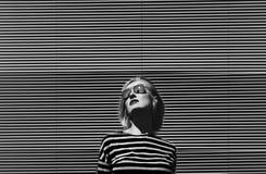 Het modieuze meisje stellen in zonnebril, op een metaal gestreepte achtergrond gekleed in gestreepte t-shirt Dag, openlucht Rebec Royalty-vrije Stock Afbeelding
