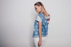 Het modieuze meisje van het hipsterblonde in Amerikaanse patriottische uitrusting en zonnebril die op grijs wordt geïsoleerd Royalty-vrije Stock Foto