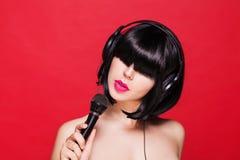 Het modieuze meisje zingen met een rode microfoon, Royalty-vrije Stock Fotografie