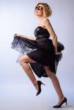 Het modieuze meisje in zonnebril en de elegante kleding van de avondontwerper, zwarte high-heeled schoenen treft een maatregel Royalty-vrije Stock Afbeeldingen