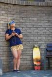 Het modieuze meisje in zonnebril luistert aan hoofdtelefoons royalty-vrije stock afbeeldingen