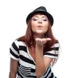 Het modieuze meisje in zwart-witte kleding geeft een kus stock afbeelding