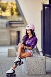 Het modieuze mooie meisje paste haar knie tijdens het rollerblading royalty-vrije stock foto's