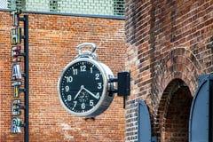 Het modieuze openbare analoge klok hangen op bakstenen muur die tijd in Brooklyn, New York tijdens dag tonen royalty-vrije stock foto
