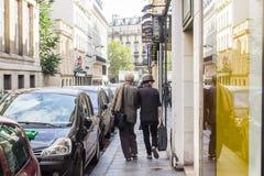 Het modieuze oudere paar wandelt onderaan de straat van Parijs Stock Foto's
