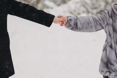 Het modieuze paar in pret hebben en liefde die dient sneeuwmou in houden royalty-vrije stock fotografie