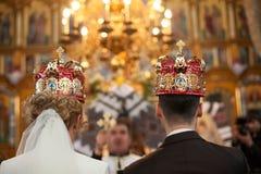 het modieuze paar van de huwelijksceremonie in de oude kerk Stock Foto