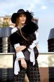 Het modieuze slanke langharige meisje kleedde zich in een zwart modieus jasje op een wit overhemd, een zwarte broek en een hoed m stock foto