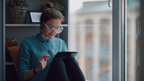 Het modieuze studentenmeisje zit door het venster op vensterbank met een gadget stock videobeelden