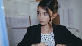 Het modieuze succesvolle meisje werkt gewillig met PC en tablet in bureau 4K stock footage