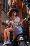 Het modieuze vrouw dragen kleden zich en de hoedenzitting op een zwarte klassieke Italiaanse autoped op een oude straat in Europa royalty-vrije stock foto's