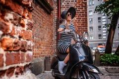 Het modieuze vrouw dragen kleden zich en de hoedenzitting op een zwarte klassieke Italiaanse autoped op een oude straat in Europa stock afbeelding
