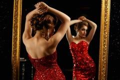 Het modieuze vrouw stellen voor spiegel stock foto