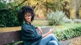 Het modieuze zwarte texting op smartphone in de herfst bij het park stock foto's