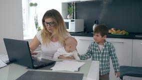 Het moederschap, mamma met baby in haar wapens berispt haar zoon die zich in thuis het werken mengt stock videobeelden