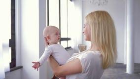 Het moederschap, mooie moeder spreekt en slingert aanbiddelijk weinig babydochter in haar wapens stock video
