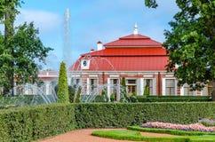 Het Monplaisir-Paleis in Peterhof, dat door groene bomen, struiken en bloemen wordt omringd Stock Foto's