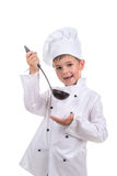 Het mooi proeft glimlachen van weinig jongen in chef-kok` s hoed met gietlepel de gekookte bouillon royalty-vrije stock foto's