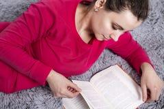 Het mooie aantrekkelijke donkerbruine meisje leest boek op comfortabele bank De hobbylezing boekt thuis Stock Foto's