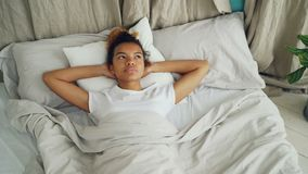 Het mooie Afrikaanse Amerikaanse meisje ligt in bed en kijkt boven dan het sluiten van haar ogen en het vallen in slaap bedtime stock video