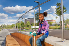 Het mooie Afrikaanse meisje houdt skateboard en zit Royalty-vrije Stock Afbeeldingen