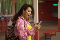 Het mooie afro Amerikaanse vrouw gebruiken mobiel in de straat Mededeling royalty-vrije stock afbeeldingen