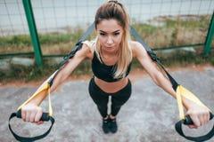 Het mooie atletenmeisje is scharnierend op de riemen, de bovenkant van sportkledingsbeenkappen In de zomer op de sportengrond in  royalty-vrije stock afbeelding