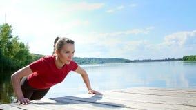 Het mooie, atletische jonge blonde vrouw uitrekken zich, die opdrukoefeningen doen Meer, rivier, blauw hemel en bos op de achterg stock video