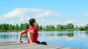 Het mooie, atletische jonge blonde vrouw uitrekken zich, die opdrukoefeningen doen Meer, rivier, blauw hemel en bos op de achterg stock footage