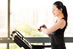 Het mooie Aziatische gebruik die van de vrouwen lopende tredmolen smartwatch luisteren Royalty-vrije Stock Afbeeldingen