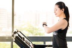 Het mooie Aziatische gebruik die van de vrouwen lopende tredmolen smartwatch luisteren Stock Afbeeldingen