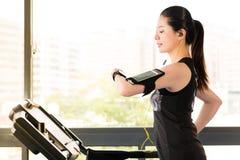 Het mooie Aziatische gebruik die van de vrouwen lopende tredmolen smartwatch luisteren Stock Foto's