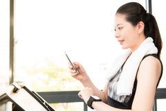 Het mooie Aziatische gebruik van de vrouwen lopende tredmolen smartwatch verbindt s Royalty-vrije Stock Foto