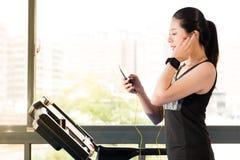 Het mooie Aziatische het gebruikssmartphone van de vrouwen lopende tredmolen luisteren Royalty-vrije Stock Foto