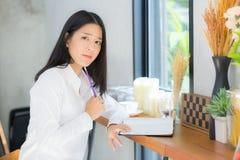 Het mooie Aziatische jonge vrouw werken online met laptop en denkt Royalty-vrije Stock Afbeelding
