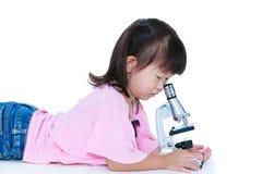 Het mooie Aziatische kind nam door een microscoop waar Geïsoleerd op wh stock foto