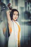Het mooie Aziatische meisjesmodel in het witte gele kleding stellen bij modern wijst glas op achtergrond Royalty-vrije Stock Afbeelding