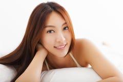 Het mooie Aziatische vrouw ontspannen op het bed Stock Foto's