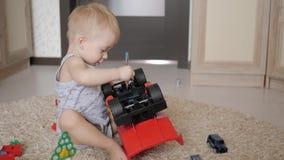 Het mooie babyjongen spelen met een groot autostuk speelgoed op vloer thuis De peuter van de jong geitjejongen het spelen met stu stock footage