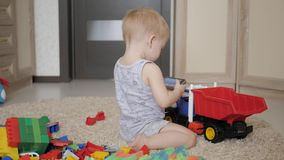 Het mooie babyjongen spelen met een groot autostuk speelgoed op vloer thuis De peuter van de jong geitjejongen het spelen met stu stock videobeelden
