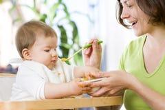 Het mooie babyjongen spelen met voedsel terwijl het eten. Stock Foto's