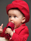 Het mooie babymeisje kleedde zich in het rode kleding eten Stock Fotografie