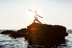 Het mooie ballerina dansen, die op rots bij strand, overzeese achtergrond stellen stock fotografie
