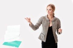 Het mooie bedrijfsvrouwenblonde in zwarte kleding, jasje liet vallen omslag van documenten op grijze achtergrond Stock Foto