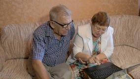 Het mooie bejaarde paar leert om aan laptop te werken stock video