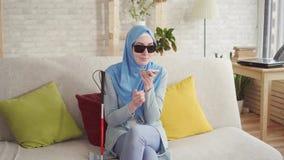 Het mooie blinde Moslimmeisje in hijab thuis, geniet van smartphone stock footage